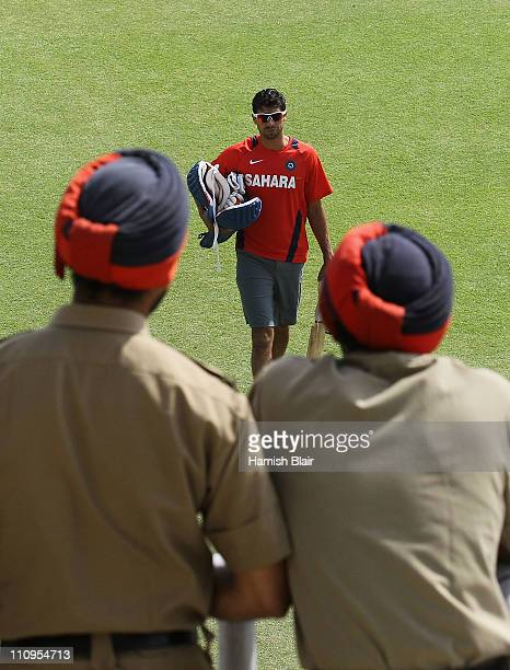 Ashish Nehra walks across the field while being watched by two policemen during an India nets session at the Punjab Cricket Association Stadium on...