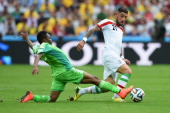 Ashkan Dejagah of Iran is challenged by Ahmed Musa of Nigeria during the 2014 FIFA World Cup Brazil Group F match between Iran and Nigeria at Arena...