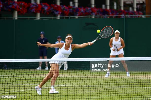Ashleigh Barty of Australia looks on as partner Casey Dellacqua of Australia plays a forehand during the Ladies Doubles first round match against...
