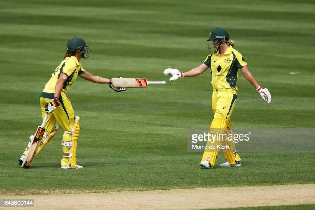 Ashleigh Gardner of Australia hands her teammate Meg Lanning her bat after she dropped it when the pair collided midpitch during the Women's Twenty20...