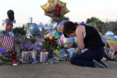 Ashleigh Grove grieves over the lost of her friend Micayla Medek at the makeshift memorial for the 12 movie theater shooting victims built across the...