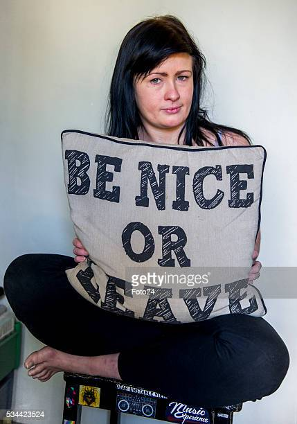 Ashleigh Schultz the Obz Café waitress who fell victim to alleged racism by a customer poses with a cushion written Be nice or leave during an...