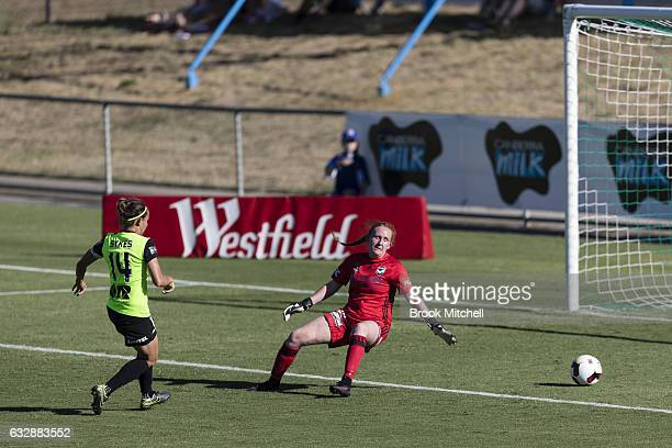 Ashleigh Sykes of Canberra United slips a ball past Melbourne Victory goal keeper Emily Kenshole to score during the round 14 WLeague match between...