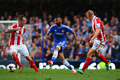 Ashley Cole of Chelsea is closed down by Charlie Adam of Stoke City and Andy Wilkinson of Stoke City during the Barclays Premier League match between...