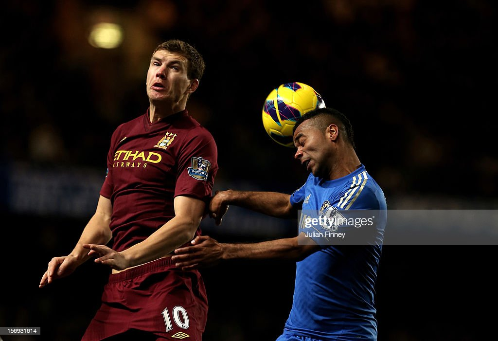 Ashley Cole of Chelsea wins a header under pressure from Edin Dzeko of Manchester City during the Barclays Premier League match between Chelsea and Manchester City at Stamford Bridge on November 25, 2012 in London, England.