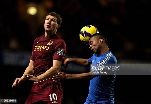 Ashley Cole of Chelsea wins a header under pressure from Edin Dzeko of Manchester City during the Barclays Premier League match between Chelsea and...
