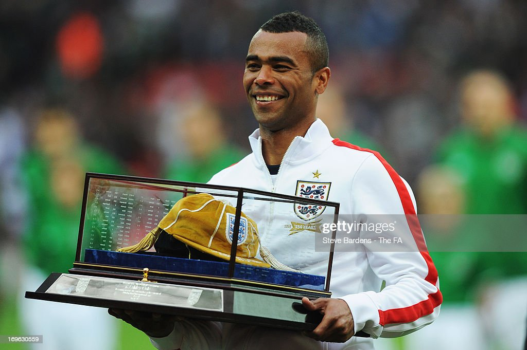 Ashley Cole of England after being presented with a commemorative golden cap by Roy Hodgson manager of England as he receives an honorary 100th cap...