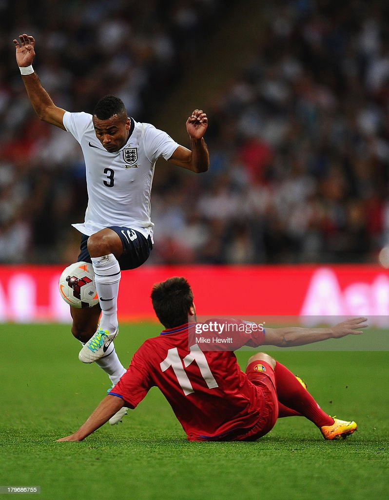 Ashley Cole of England leaps over a challenge from Serghei Georghiev of Moldova during the FIFA 2014 World Cup Qualifying Group H match between England and Moldova at Wembley Stadium on September 6, 2013 in London, England.
