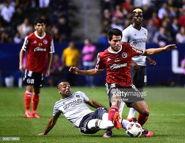 Ashley Cole of the Los Angeles Galaxy attempts to kick the ball from Hiram Munoz of Club Tijuana during the first half at StubHub Center on February...