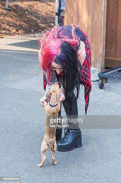 Ashley Costello of New Years Day holds a puppy brought by Motley Zoo Animal Rescue during Pain In The Grass hosted by 999 KISW at White River...