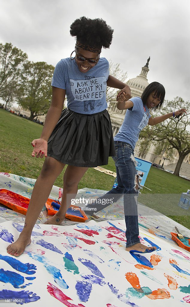 Ashley Dike, left, and Zikea McCurdie, juniors from Howard University, make painted footprints on a canvas during an event on the east front of the Capitol hosted by International Relief & Development and TOMS shoes, to promote good health for children around the world by providing shoes.