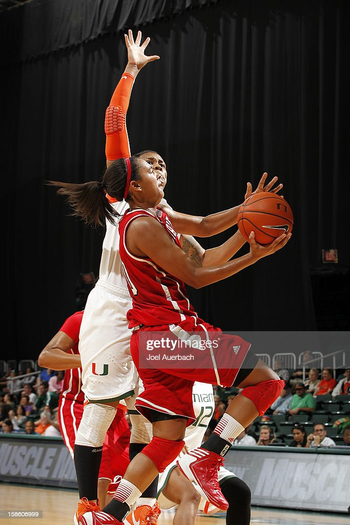 Ashley Eli #10 of the North Carolina State Wolfpack goes to the basket against Maria Brown #50 of the Miami Hurricanes on December 20, 2012 at the BankUnited Center in Coral Gables, Florida. The Hurricanes defeated the Wolfpack 79-53.