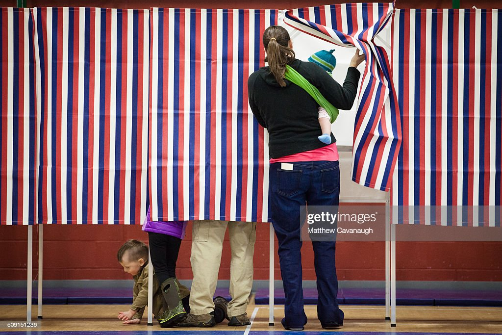 Ashley Grover (R) along with her husband and children, enters a voting booth on February 9, 2016 at Broken Ground School in Concord, NH. Voters throughout the state are heading to the polls as the New Hampshire Primary, also known as the first-in-the-nation primary, continues the process of selecting the next president of the United States.