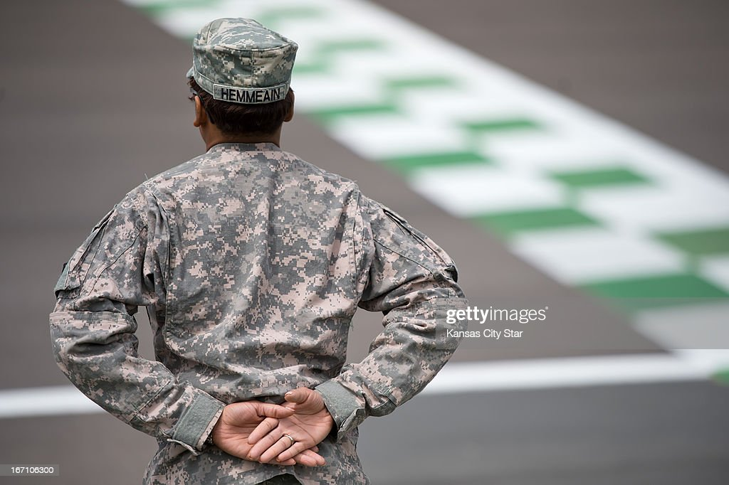 Ashley Hemmeain with the Army's 8th Legal Operations Detachment in Independence, Missouri, stands at attention near the finish line prior to the NASCAR Camping World Truck Series' SPF 250 on Saturday, April 20, 2013, at Kansas Speedway in Kansas City, Kansas.