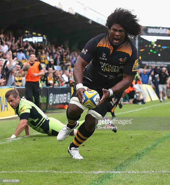 Ashley Johnson of Wasps breaks away from Stephen Myler to score the first try during the Aviva Premiership match between Wasps and Northampton Saints...