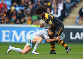 Ashley Johnson of Wasps is tackled by Kahn Fotuali'i of Northampton Saints during the Aviva Premiership match between Wasps and Northampton Saints at...