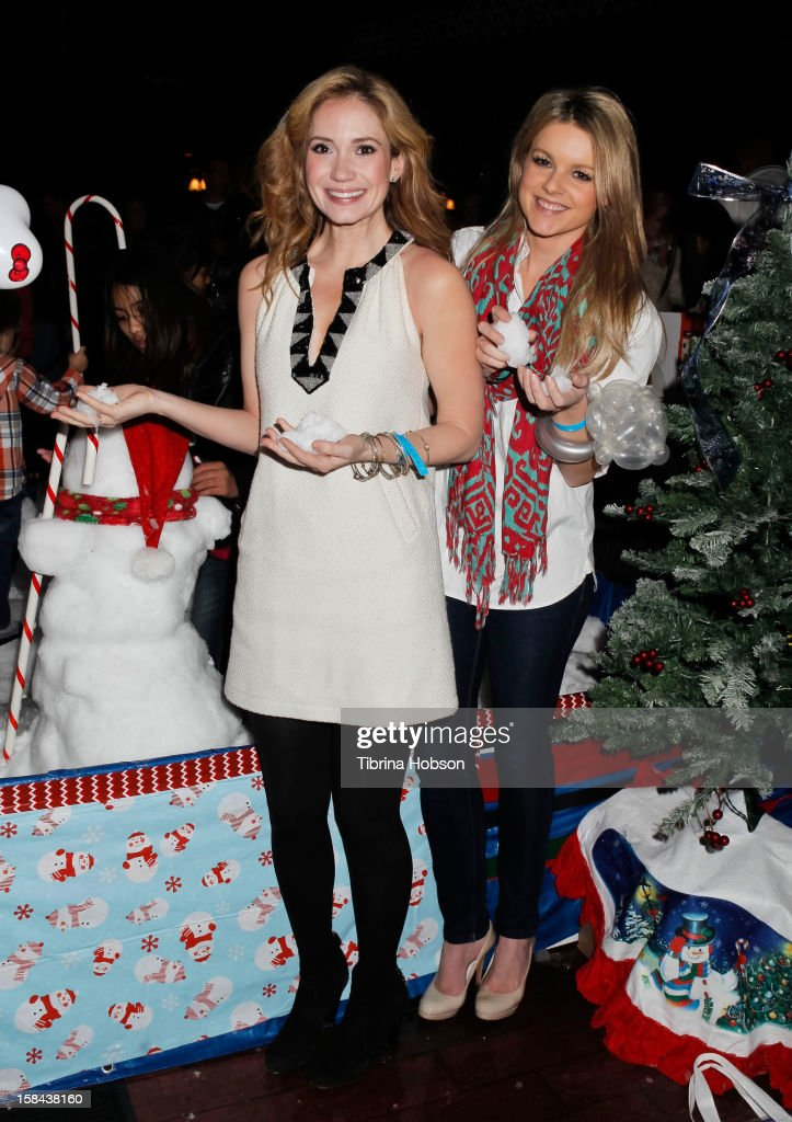 Ashley Jones and Ali Fedotowsky play in the snow at the Truehearts winter wonderland charity gala, benefiting Children's Hospital Los Angeles at Avalon on December 16, 2012 in Hollywood, California.