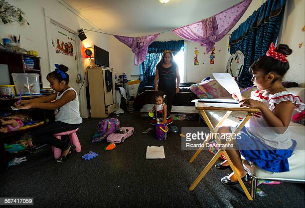LOS ANGELES CA MARCH 27 2014 Ashley Orosco Lt and sister Lindsay doing their homework while their mother Melina Vasquez care for their little sister...