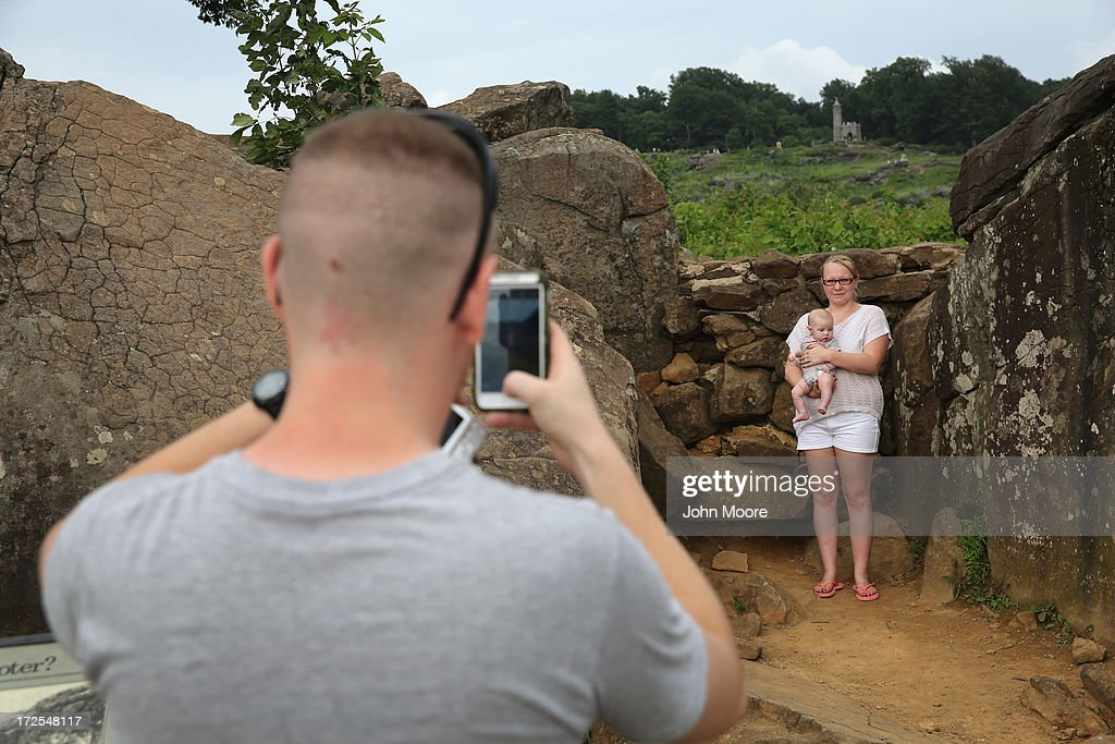 Ashley Rosen, 22, holds her daughter Adriana, 3 months, poses for a photo at Devil's Den on July 2, 2013 in Gettysburg, Pennsylvania, the 150th anniversary of the Battle of Gettysburg. Many tourists visiting the site pose for photos there as part of their battlefield experience. An historic photo entitled 'The Home of a Rebel Sharpshooter' was taken there by Alexander Gardner on July 5, 1863 and featured a dead Confederate soldier with a rifle proped next to him. The photograph was later discovered to be staged, the dead body of the 'sharpshooter' having been brought from another place on the battlefield for the photograph and the gun not a sharps rifle.