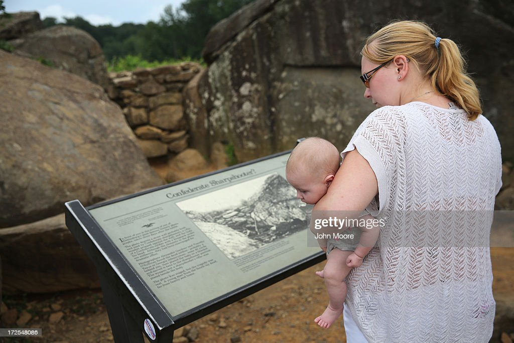 Ashley Rosen, 22, holds her daughter Adriana, 3 months, while reading the story of 'The Home of a Rebel Sharpshooter' photograph at Devil's Den on July 2, 2013 in Gettysburg, Pennsylvania, the 150th anniversary of the Battle of Gettysburg. Many tourists visiting the site pose for photos there as part of their battlefield experience. An historic photo entitled 'The Home of a Rebel Sharpshooter' was taken there by Alexander Gardner on July 5, 1863 and featured a dead Confederate soldier with a rifle proped next to him. The photograph was later discovered to be staged, the dead body of the 'sharpshooter' having been brought from another place on the battlefield for the photograph and the gun not a sharps rifle.