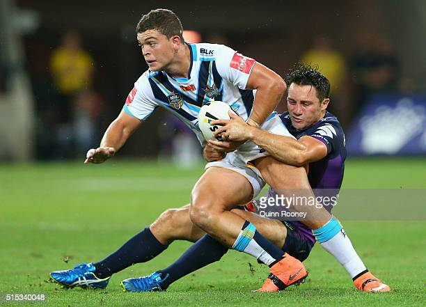 Ashley Taylor of the Titans is tackled by Cooper Cronk of the Storm during the round two NRL match between the Melbourne Storm and the Gold Coast...