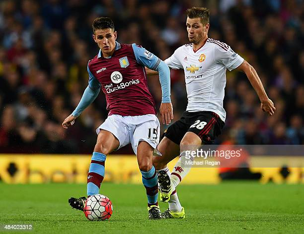 Ashley Westwood of Aston Villa is tackled by Morgan Schneiderlin of Manchester United during the Barclays Premier League match between Aston Villa...