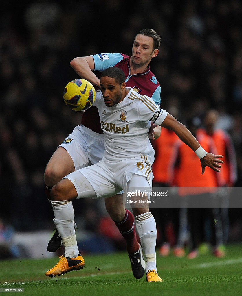 Ashley Williams of Swansea City and Kevin Nolan of West Ham United challenge for the ball during the Barclays Premier League match between West Ham United and Swansea at the Boleyn Ground on February 2, 2013 in London, England.