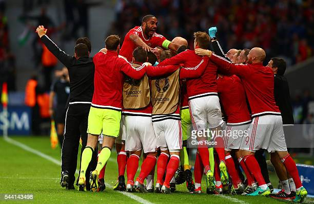Ashley Williams of Wales dives to his team mates and staffs to celebrate scoring his team's first goal during the UEFA EURO 2016 quarter final match...