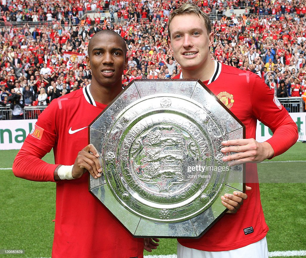 Ashley Young (L) and Phil Jones of Manchester United pose with the Community Shield trophy after the FA Community Shield match between Manchester City and Manchester United at Wembley Stadium on August 7, 2011 in London, England.