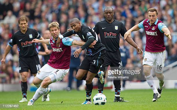 Ashley Young of Aston Villa is challenged by Thomas Hitzlsperger of West Ham United during the Barclays Premier League match between West Ham United...