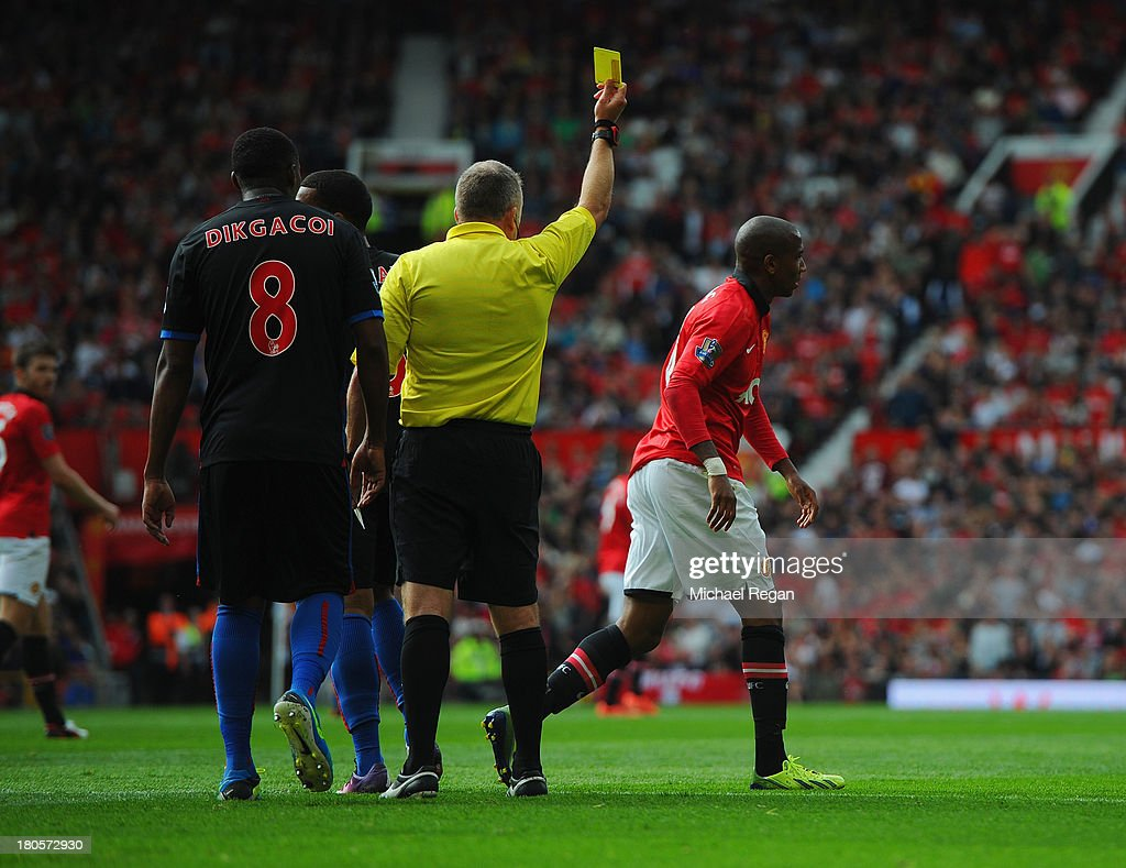 Ashley Young of Manchester United is booked by referee Jonathan Moss for diving during the Barclays Premier League match between Manchester United...