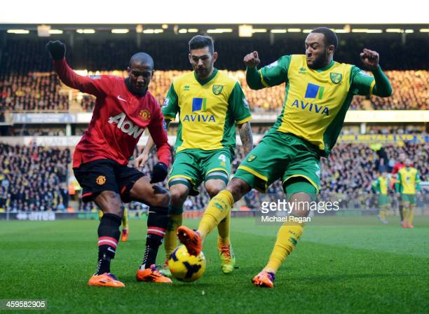 Ashley Young of Manchester United is challenged by Bradley Johnson and Nathan Redmond of Norwich City during the Barclays Premier League match...