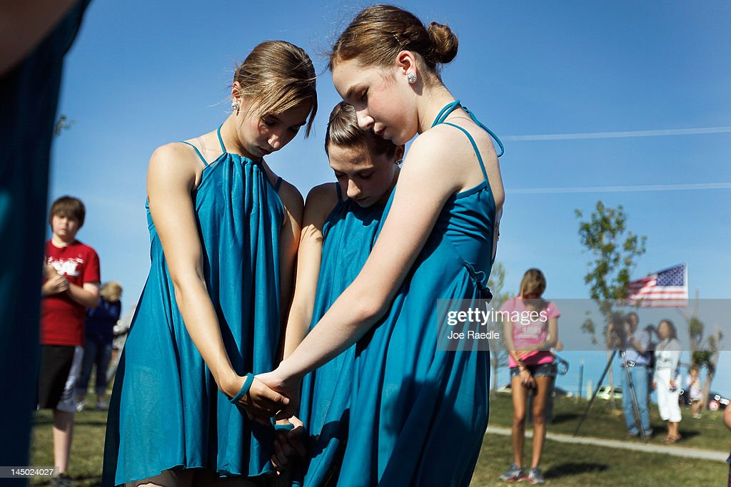 Ashlyn Griffberg, Sierra Roper and Samantha Vance from the Sensations Performing Arts Studio pray together in Cunningham Park during ceremony that included a moment of silence at 5:41 p.m. which was when the monstrous tornado first hit the city a year ago to the day on May 22, 2012 in Joplin, Missouri. The EF-5 tornado devastated the area leaving behind a path of destruction along with 161 deaths and hundreds of injuries, but one year later there are signs that the town is beginning to recover.