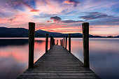 Ashness Jetty at Derwentwater, Keswick, Lake District, UK. The image features a wide angle view of the jetty with a stunning pink and purple dramatic sunset.