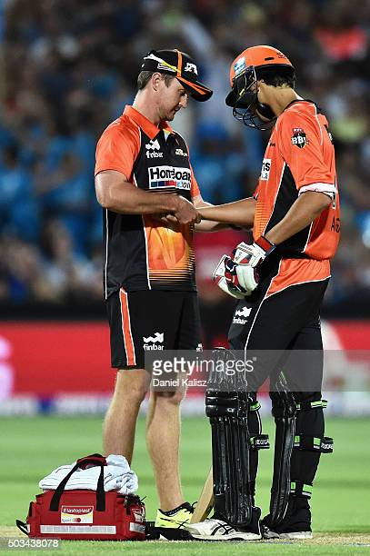 Ashton Agar of the Scorchers receives treatment from the team doctor after being struck on the arm by a delivery from Billy Stanlake of the Adelaide...