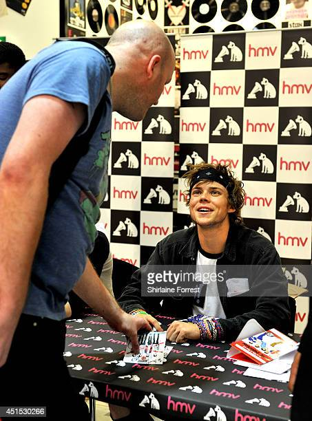 Ashton Irwin of 5 Seconds Of Summer signs copies of their debut self titled album at HMV on June 30 2014 in Manchester England