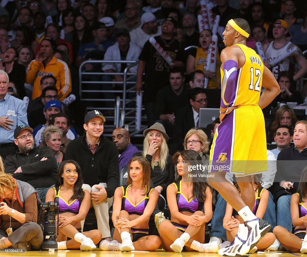 Ashton Kutcher (L) and Kaley Cuoco speak to Dwight Howard at a basketball game between the Indiana Pacers and the Los Angeles Lakers at Staples Center on November 27, 2012 in Los Angeles, California.