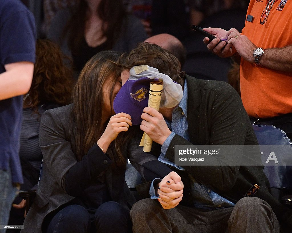 Ashton Kutcher and Mila Kunis attend a basketball game between the Utah Jazz and the Los Angeles Lakers at Staples Center on January 3 2014 in Los...