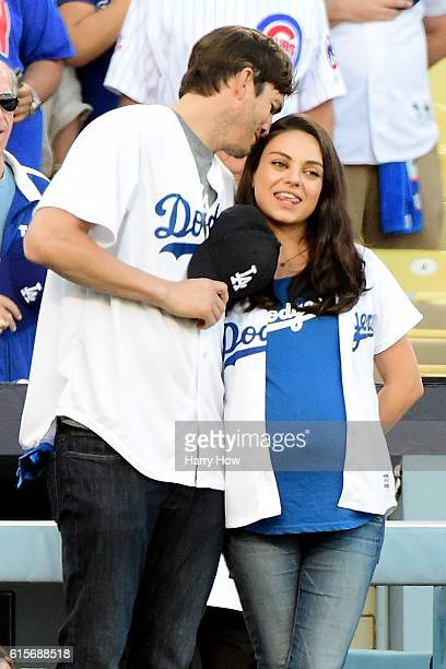 Ashton Kutcher and wife Mila Kunis on the field after they announced the Los Angeles Dodgers starting lineup before game four of the National League...
