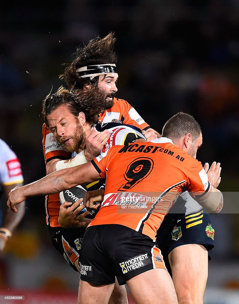 Ashton Sims of the Cowboys is tackled by Aaron Woods and Robbie Farah of the Tigers during the round 22 NRL match between the North Queensland Cowboys and the Wests Tigers at 1300SMILES Stadium on August 9, 2014 in Townsville, Australia.