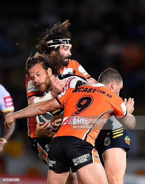 Ashton Sims of the Cowboys is tackled by Aaron Woods and Robbie Farah of the Tigers during the round 22 NRL match between the North Queensland...