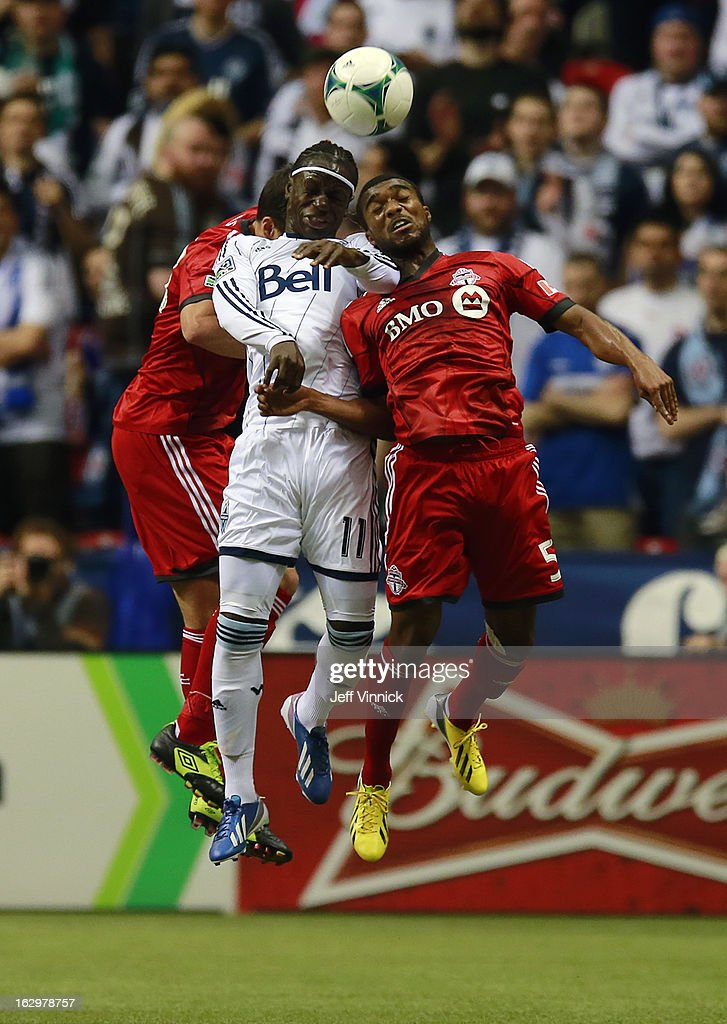 Ashtone Morgan #5 of the Toronto FC and Darren Mattocks #11 of the Vancouver Whitecaps FC take to the air to play the ball during their MLS game March 2, 2013 at B.C. Place in Vancouver, British Columbia, Canada.