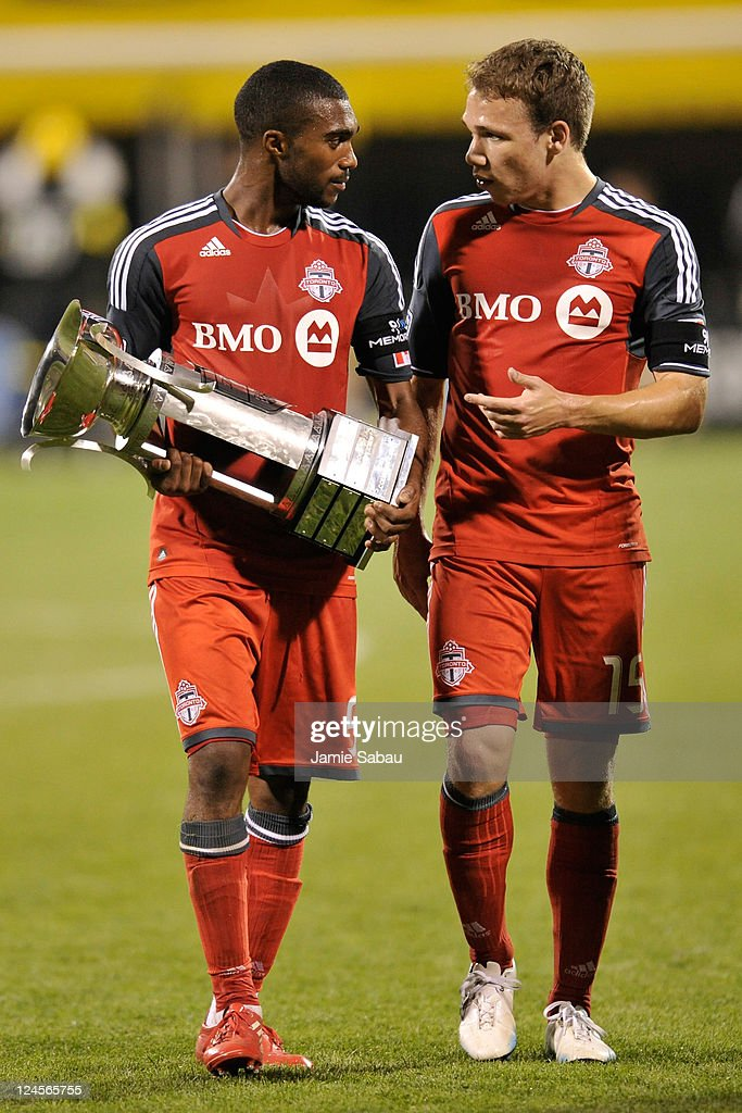 Ashtone Morgan #5 of Toronto FC carries the Trillium Cup as he and Matt Stinson #15 of Toronto FC walk off the field after Toronto FC defeated the Columbus Crew 4-2 on September 10, 2011 at Crew Stadium in Columbus, Ohio. Toronto won the Trillium Cup for the first time.