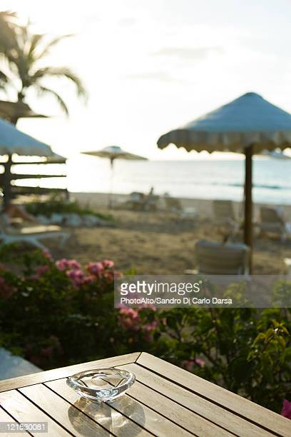 Ashtray on table at beach, beach umbrellas and deckchairs in background