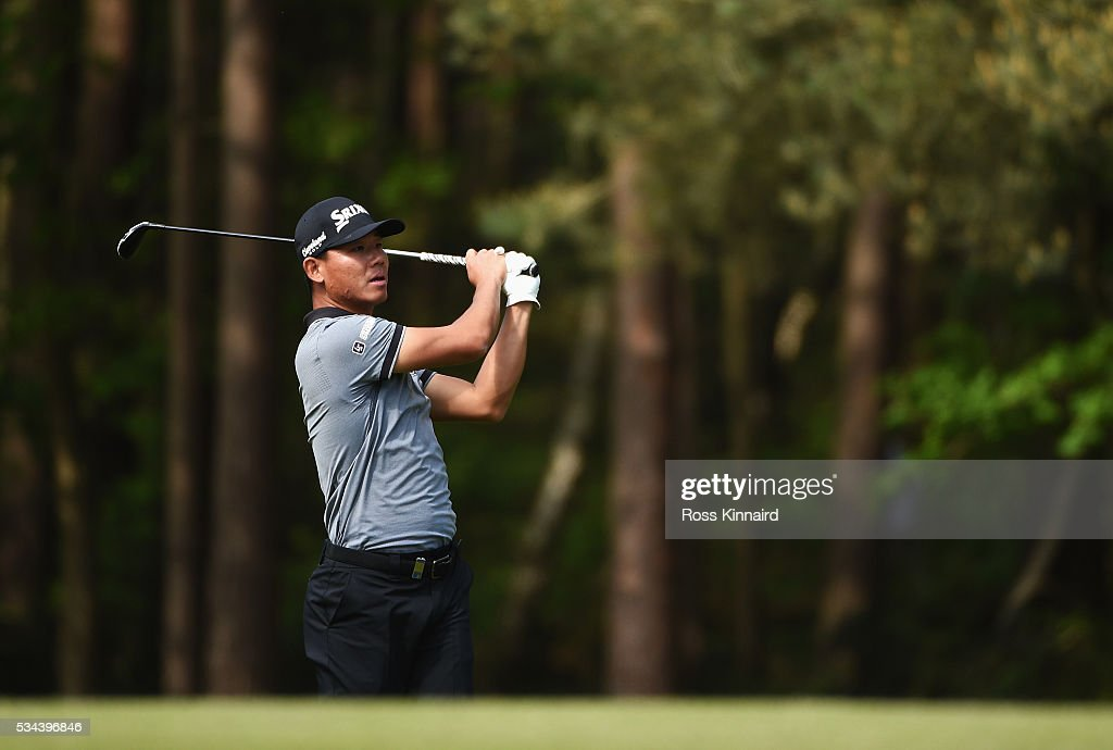 Ashun Wu of China hits his 2nd shot on the 13th hole during day one of the BMW PGA Championship at Wentworth on May 26, 2016 in Virginia Water, England.