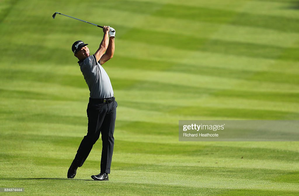 Ashun Wu of China hits his approach on the 4th hole during day one of the BMW PGA Championship at Wentworth on May 26, 2016 in Virginia Water, England.