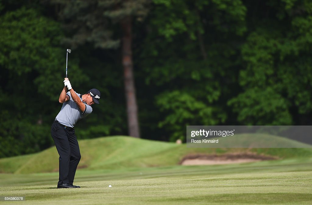 Ashun Wu of China hits his approach on the 6th hole during day one of the BMW PGA Championship at Wentworth on May 26, 2016 in Virginia Water, England.
