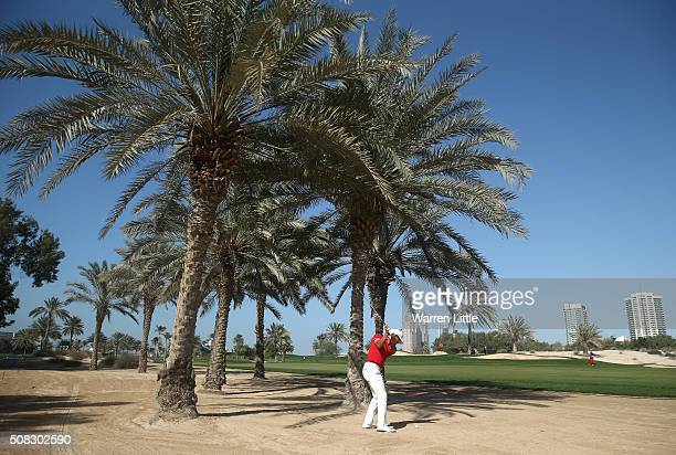 Ashun Wu of China lays his second shot on the 12th hole during the first round of the Omega Dubai Desert Classic at The Emirates Golf Club on...
