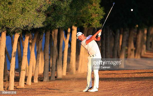 Ashun Wu of China plays his second shot at the par 5 10th hole during the second round of the 2016 Omega Dubai Desert Classic on the Majlis Course at...