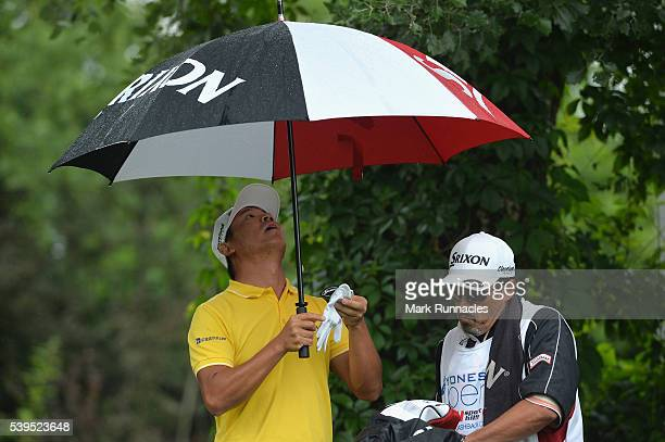 Ashun Wu of China stands under an umbrella on the 4th hole during the final round of the Lyoness Open at Diamond Country Club on June 12 2016 in...
